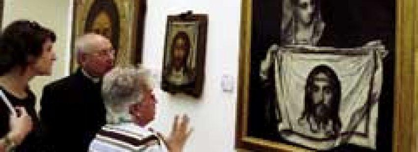 dos personas delante de un cuadro de temática religiosa