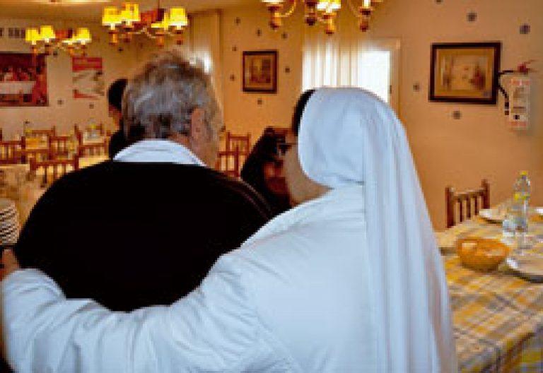 religiosa ayuda a un anciano en un centro de Cáritas