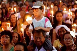 familias en Filipinas con velas en una celebración religiosa