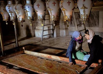 dos jóvenes sentadas junto al Santo Sepulcro en Jerusalén