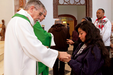 sacerdotes da la comunión a un grupo de inmigrantes de la parroquia