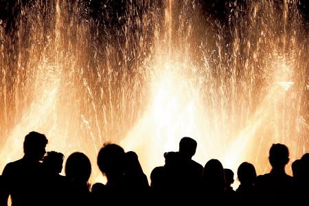 grupo de personas en espectáculo de fuentes de agua con luz