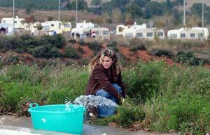 mujer sin techo cogiendo agua con una manguera