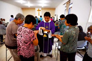 grupo de fieles católicos chinos reciben la comunión