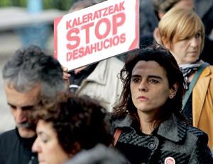 chica con un cartel en una protesta stop desahucios