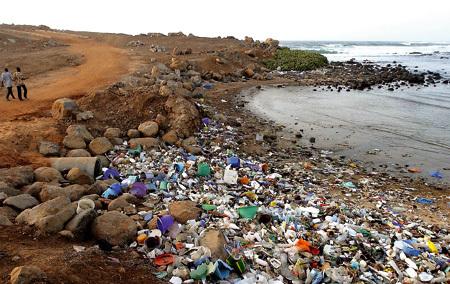 dos personas pasean al lado de una playa contaminada basura en la orilla
