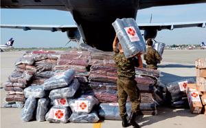 soldados polacos descargando de un avión ayuda humanitaria enviada por Cáritas