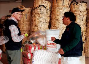 dos personas gestionando enseres de ayuda humanitaria enviada por Cáritas
