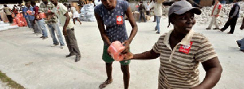 cadena de voluntarios recogiendo ayuda humanitaria internacional enviada por Cáritas