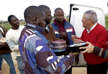 un hombre da tarteras con comida a un grupo de inmigrantes