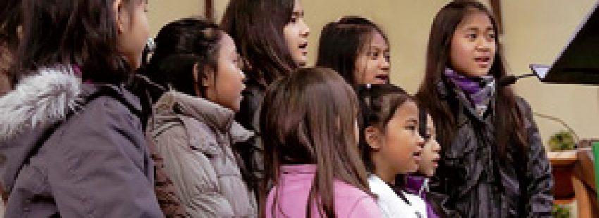grupo de niñas inmigrantes en el coro de la parroquia