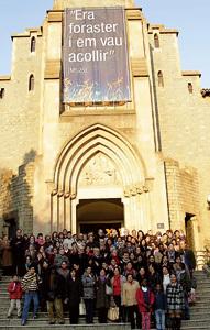 grupo de españoles e inmigrantes posan en la fachada de una iglesia por la integración