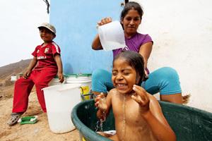 mujer madre bañando a niños en Perú