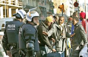 dos policias piden documentación a grupo de varios inmigrantes