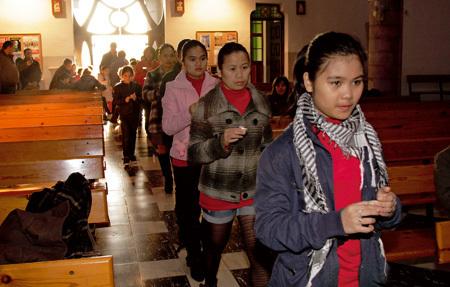 chicas jóvenes inmigrantes entrando en procesión en una iglesia en Cataluña