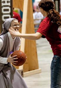 una religiosa juega al baloncesto con una chica