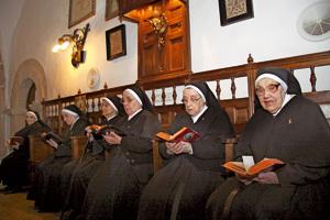 grupo de religiosas mayores rezando en la capilla