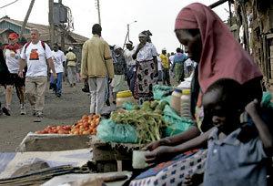 mujer con niño vendiendo fruta en un mercado en África