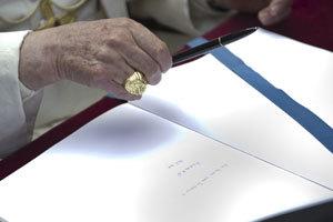 papa Benedicto XVI firma en un libro