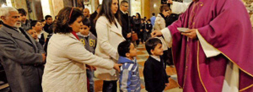 párroco durante la imposición de la ceniza a niños y fieles
