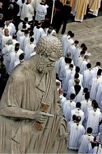 sacerdotes al lado de la estatua de san Pedro