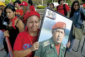mujer venezolana con retrato de Hugo Chávez