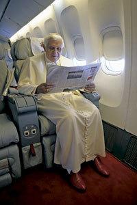 papa Benedicto XVI leyendo el periódico en el avión papal
