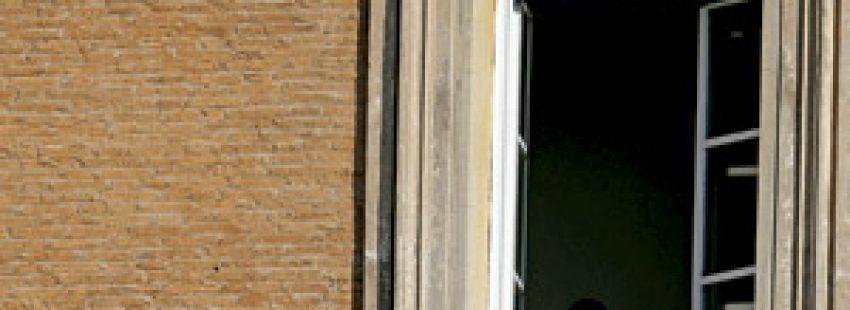 religiosa apoyada en una ventana