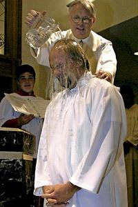 sacerdote bautiza a un hombre adulto