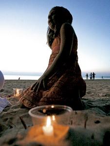 chica joven en la playa con una vela encendida