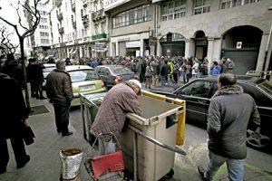 grupo de personas se manifiestan en la calle mientras un hombre busca en un contenedor