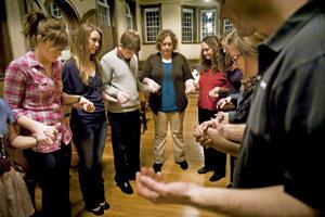 grupo de jóvenes en círculo rezando cogidos de las manos