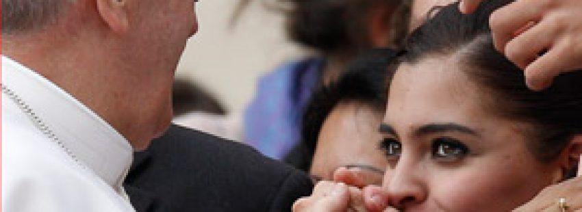 una mujer besa la mano del papa Francisco