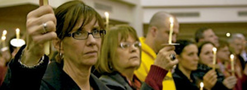 mujeres en una iglesia portan velas