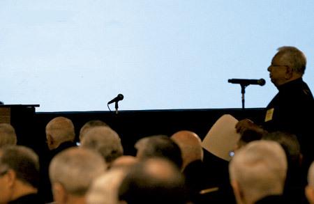sacerdote pronuncia una conferencia desde un micrófono ante el público