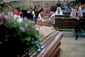 mujer reza ante el féretro del obispo Juan Gerardi asesinado en Guatemala