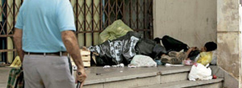 niño joven sin techo durmiendo en la calle entre cartones