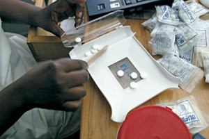 médico africano manipula pastillas