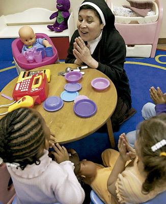 religiosa con hábito juega con niñas pequeñas