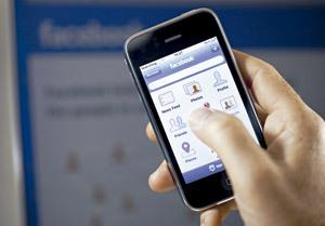 usuario con teléfono móvil entrando en Facebook