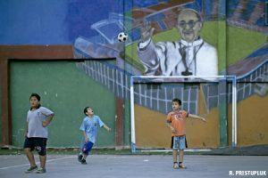 niños juegan en campo de fútbol en villa miseria en Buenos Aires