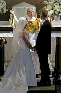 un sacerdote oficia la boda católica mientras los novios están cogidos de la mano
