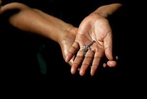 mujer sostiene crucifijo pequeño entre sus manos