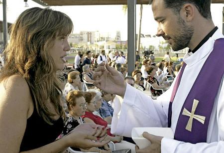 sacerdote da la comunión a una chica