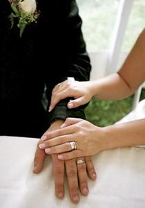 novios recién casados acariciándose las manos con las alianzas puestas