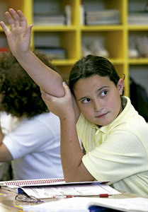 niña alumna con la mano alzada en clase en el colegio