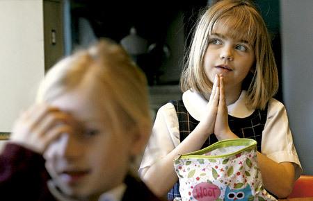dos niñas rezando en clase de religión en la escuela