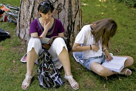 mujer y chica joven leyendo libros al aire libre en el parque