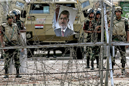 Egipto tras el golpe de estado el ejército guarda una verja en la que cuelga la foto de Mursi