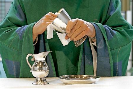 sacerdote limpia el cáliz sobre el altar